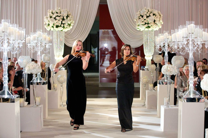 violinists performing and playing at a wedding event while walking down the aisle