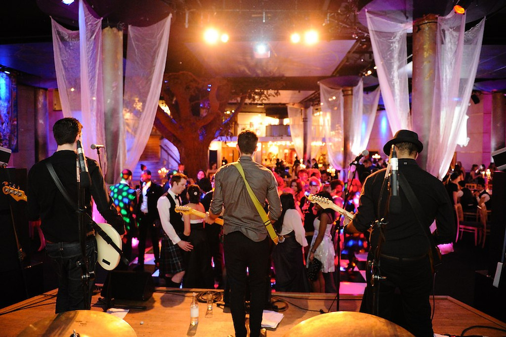 rock band with 3 guitarists and bass players performing on stage at a wedding party