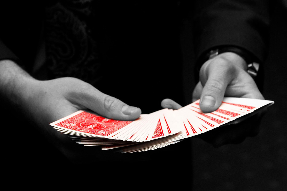 magician stacks and mixes up red playing cards ready to perform some magic