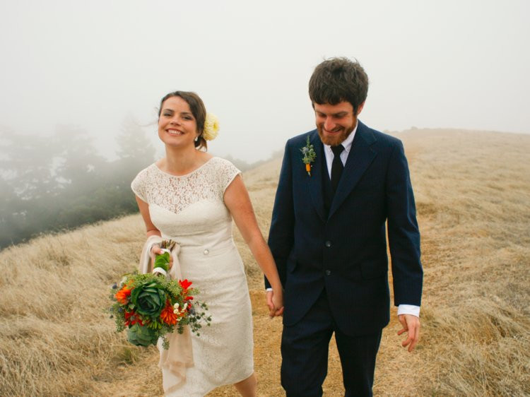 bride and groom walking across the fields while holding hands