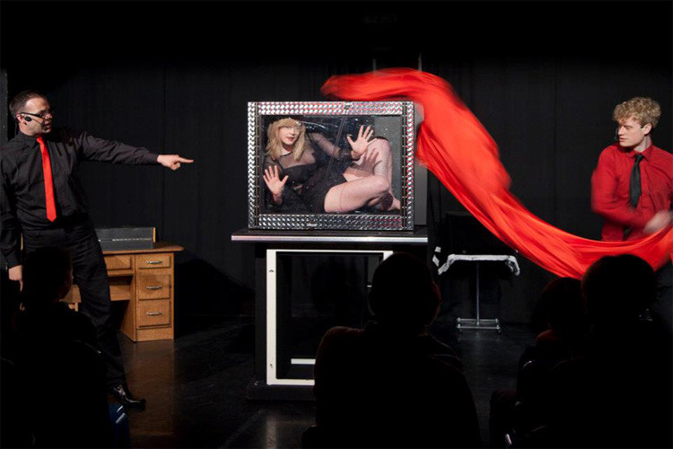 two magicians reveal female magician assistant in a see through box and a red cloth
