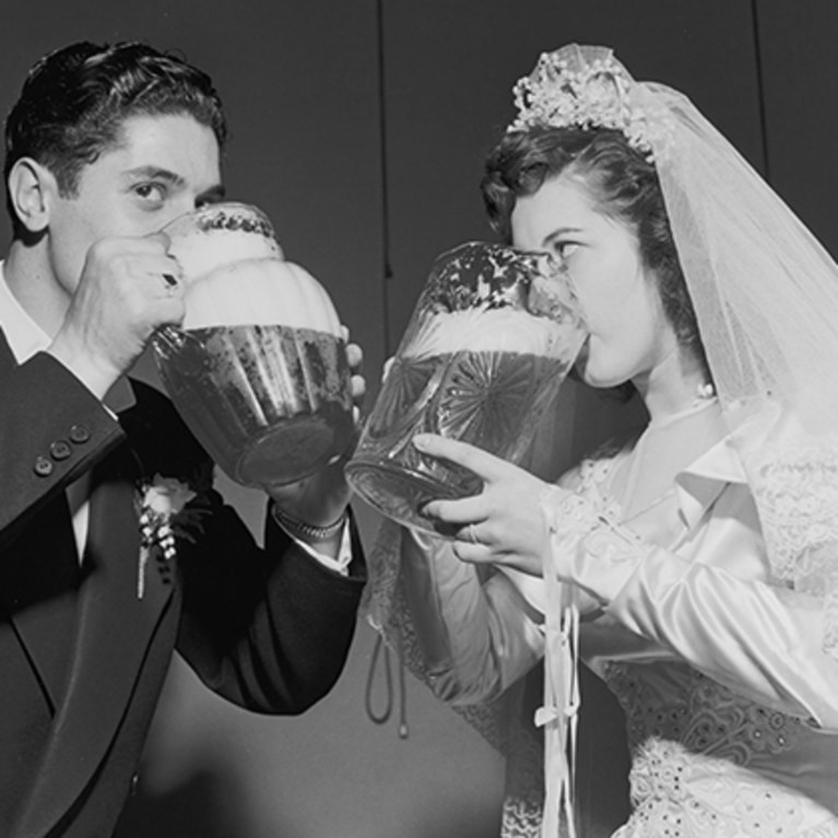 old historic black and white picture of a bride and groom drinking a big jug of beer