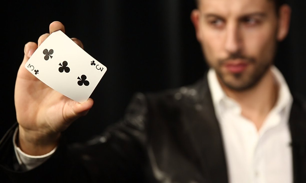 Magician performs a close-up card trick with a black 3 of clubs