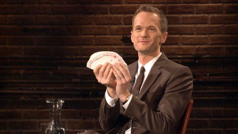 Neil Patrick Harris spreading out and holding a deck of playing cards whilst sitting down