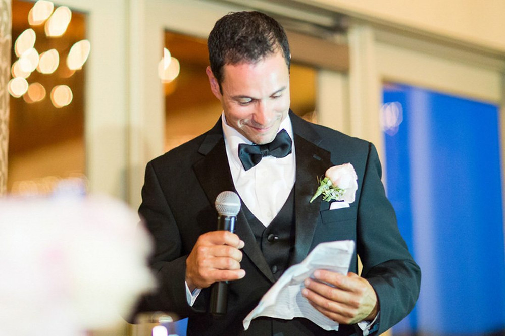 best man in a black suit giving out a speech at a wedding