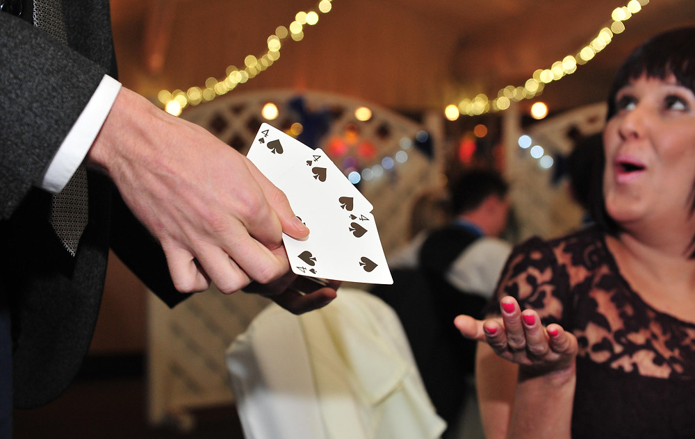 magician handing over cards to assistant in a close up magic trick