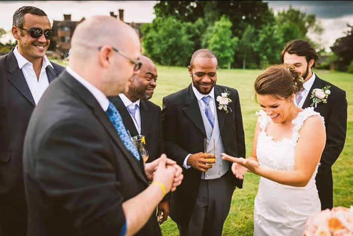 a slightly unusual magician performs close up magic for a bride at a wedding event