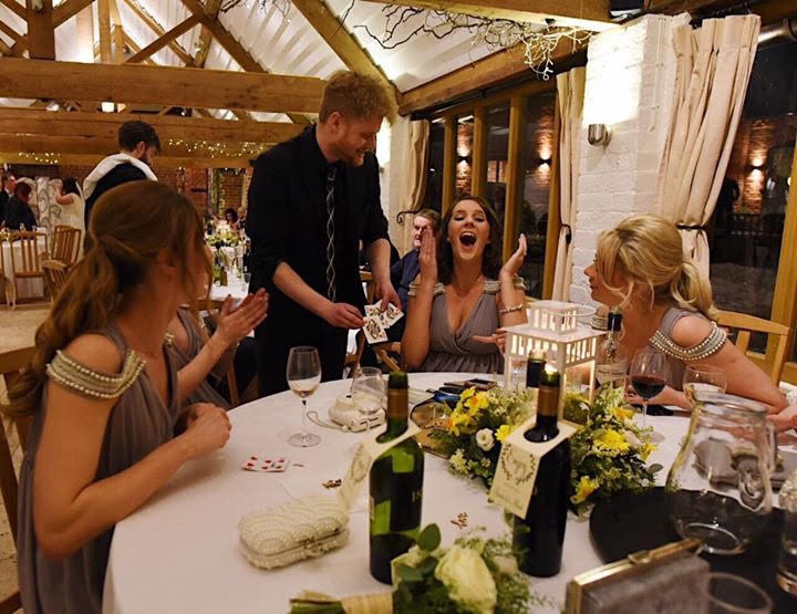magician performs a close-up magic card trick for women at a wedding party