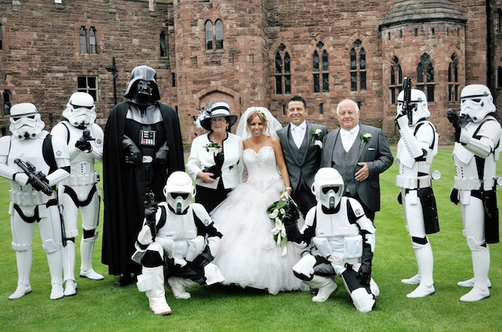 A Star wars themed wedding with bride, groom, star troopers & darth vader posing for the camera