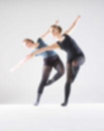 twee meisjes in danskleren die een modern jazz pose doen op grijze achtergrond