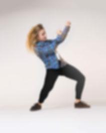 Stoere danseres met straatkleren in een urban dance pose op een grijze achtergrond