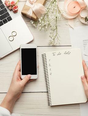 Wedding arrangement background. Female hands preparing for marriage, using laptop, smartph