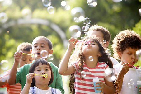 Preschool children blowing bubbles