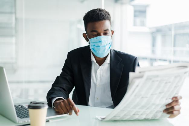 Homem lendo jornal com máscara no rosto
