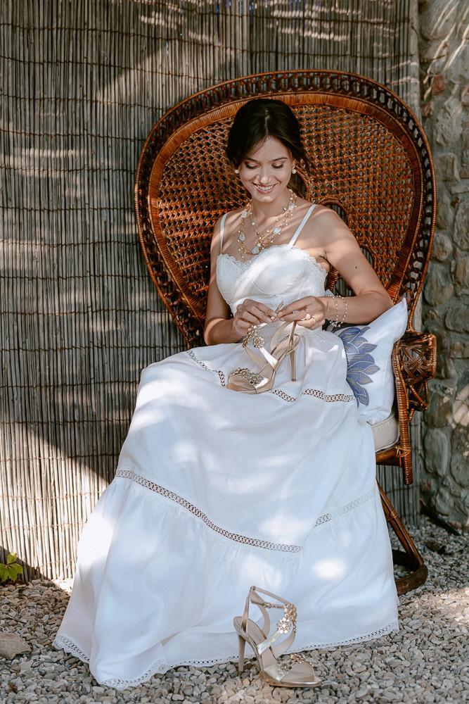 La sposa si prepara per la festa di fidanzamento, indossando un abito in organza di cotone e merletti, fatto interamente a  mano a Firenze da Andreia Cruz