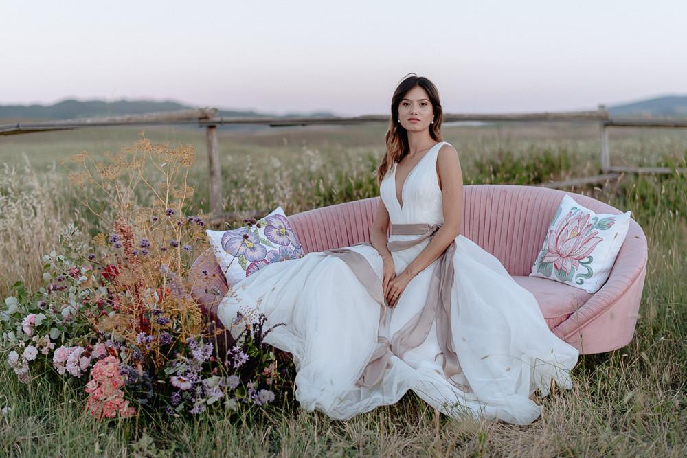 sposa sul divano nel Val D'Orcia, indossa abito da sposa in tulle, interamente fatto a mano da Andreia Cruz
