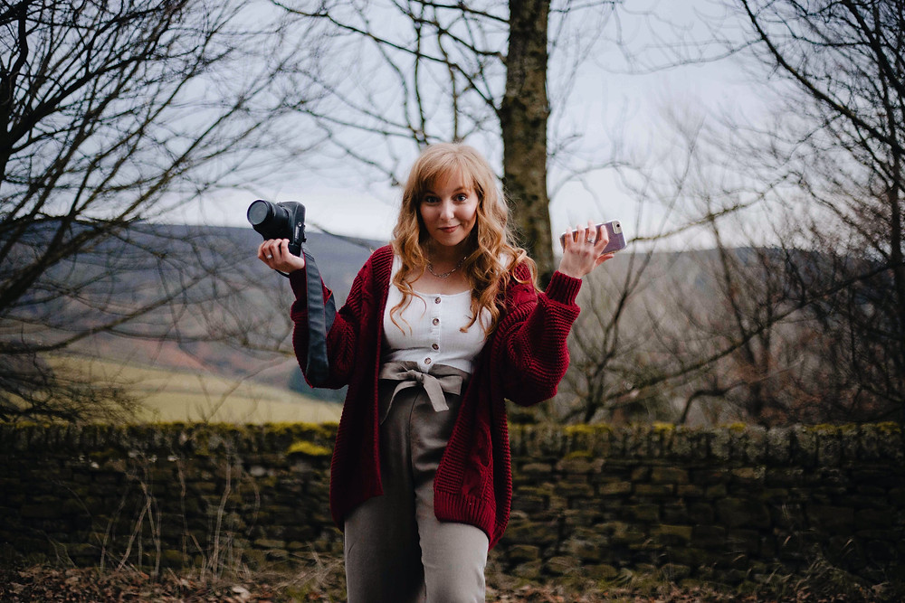 A young woman in the woods holding up her DSLR camera and her iphone looking jokingly confused and smiling
