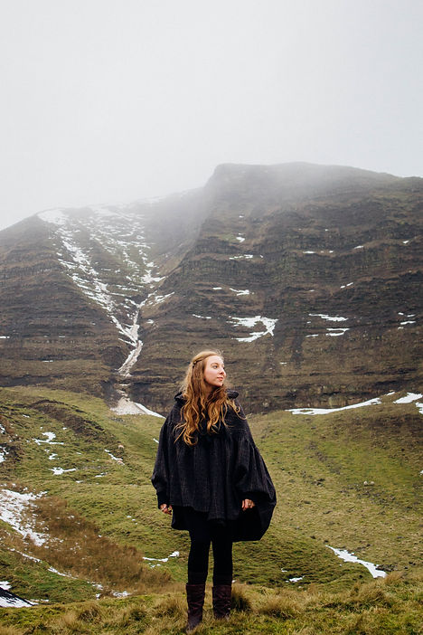 A young woman in a grey cloak staring out into the misty mountains