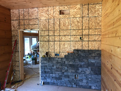 Putting in some exterior stone as a dramatic lift to the library - custom mantle out of some log scraps on top