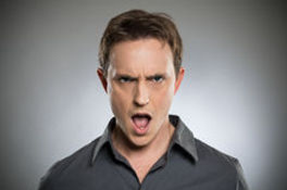 angry-young-man-shouting-portrait-over-g
