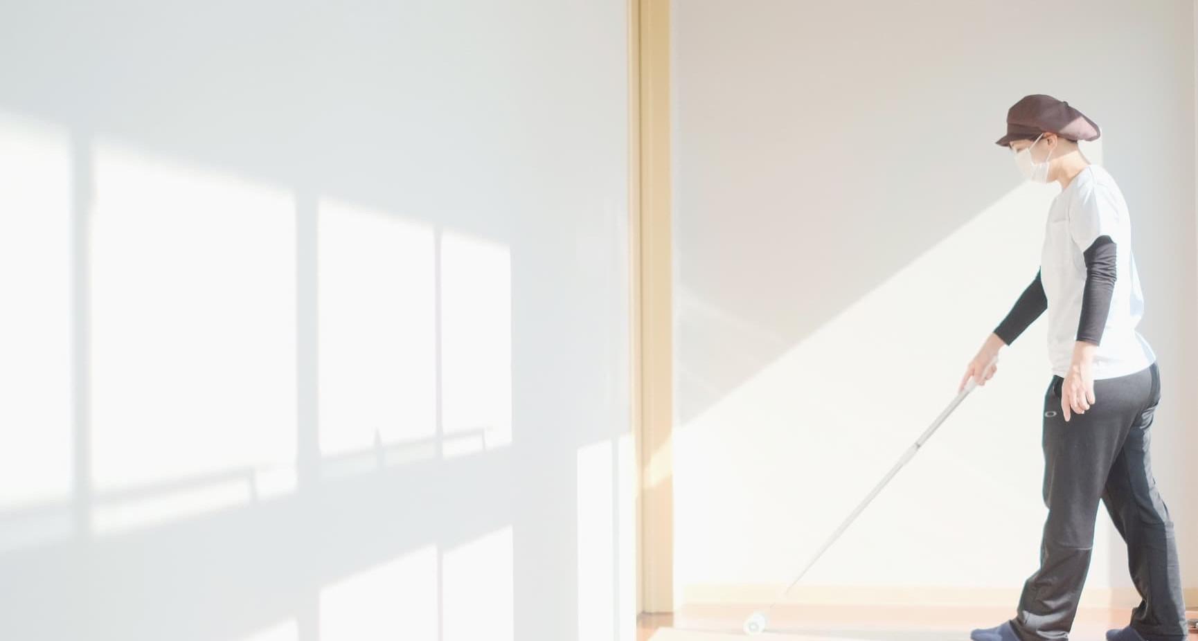 光のあたる廊下を清掃するスタッフ