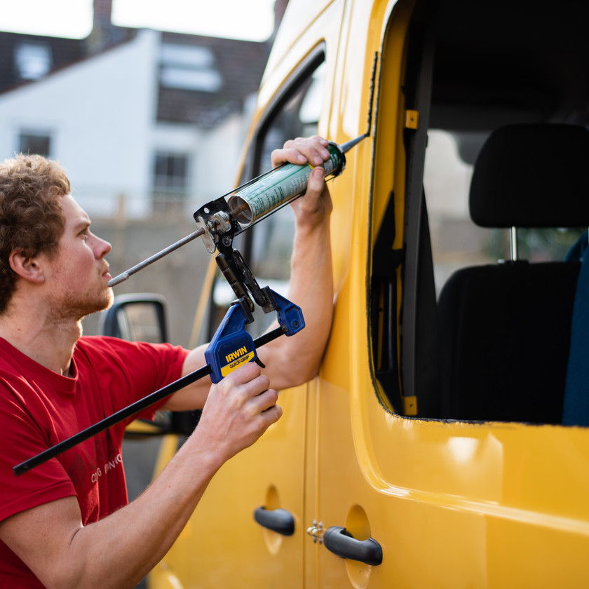 man putting glue on the side of a van conversion in order to install windows