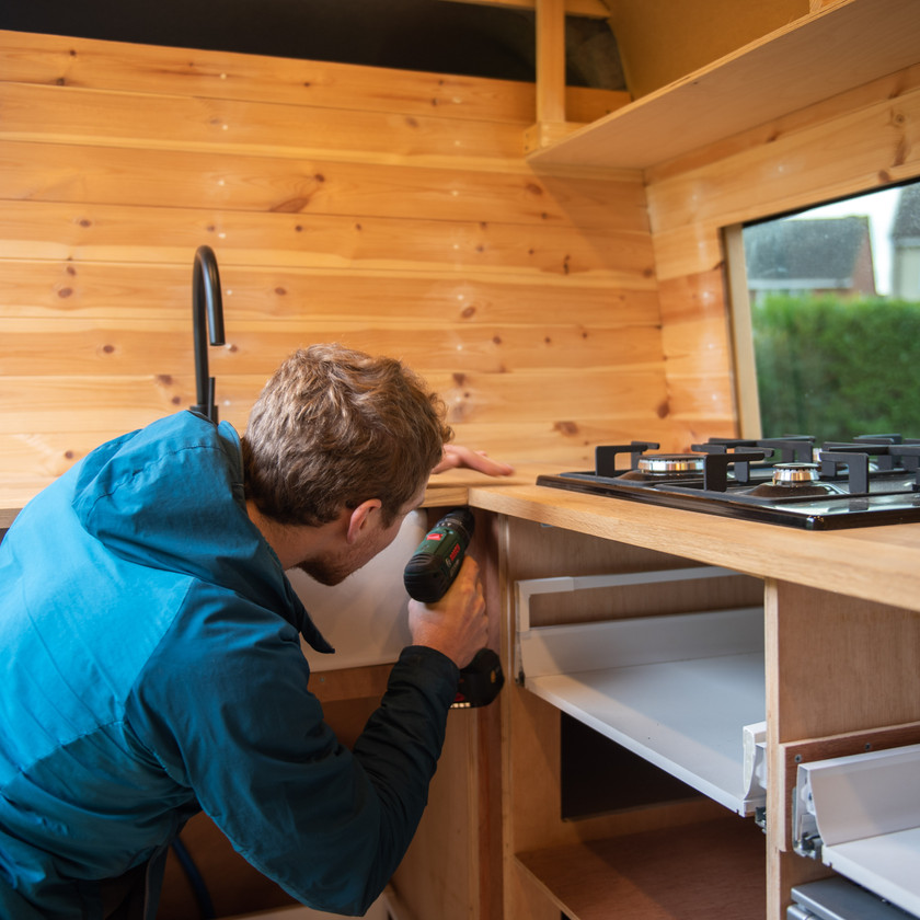 Man fitting a kitchen with a Belfast sink in a camper van conversion