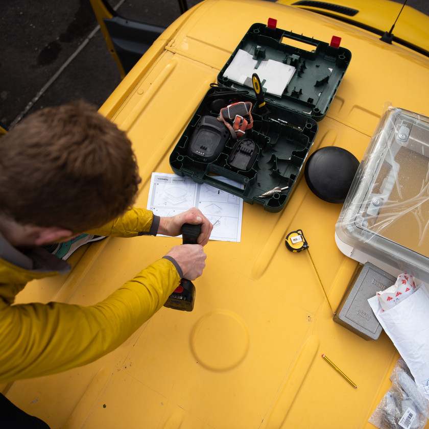 man drilling a hole in a yellow Sprinter van conversion to install a skylight