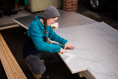 girl cutting Celotex Recticel thermal insulation boards with a saw
