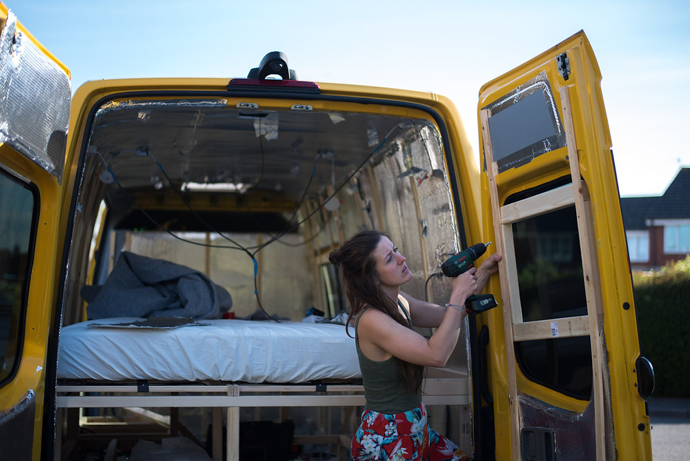 Girl screwing a window frame into place on a Sprinter van conversion