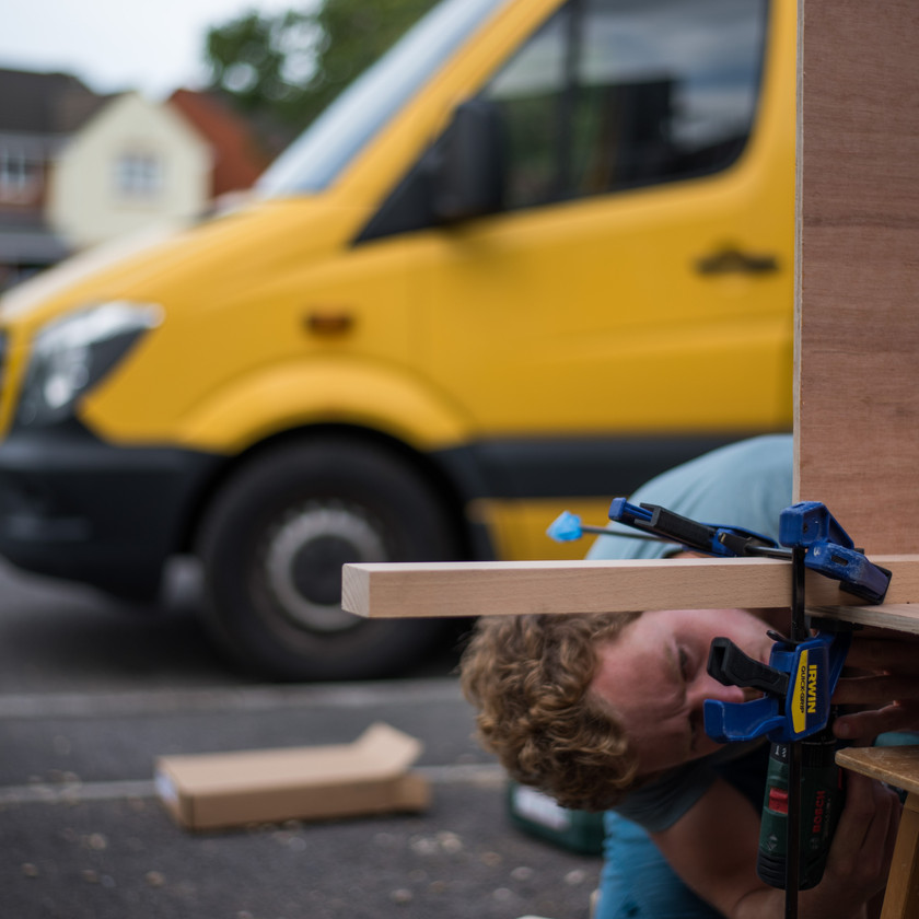 Man building a camper van kitchen our of ply
