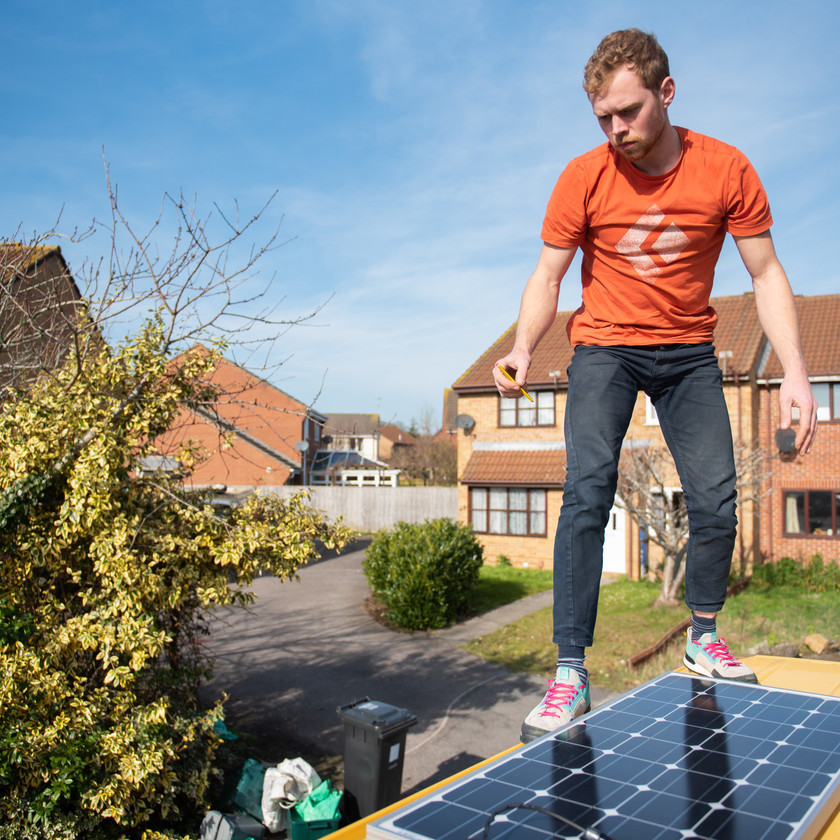 man stood on top of a Merdeces Sprinter van conversion installing solar panels