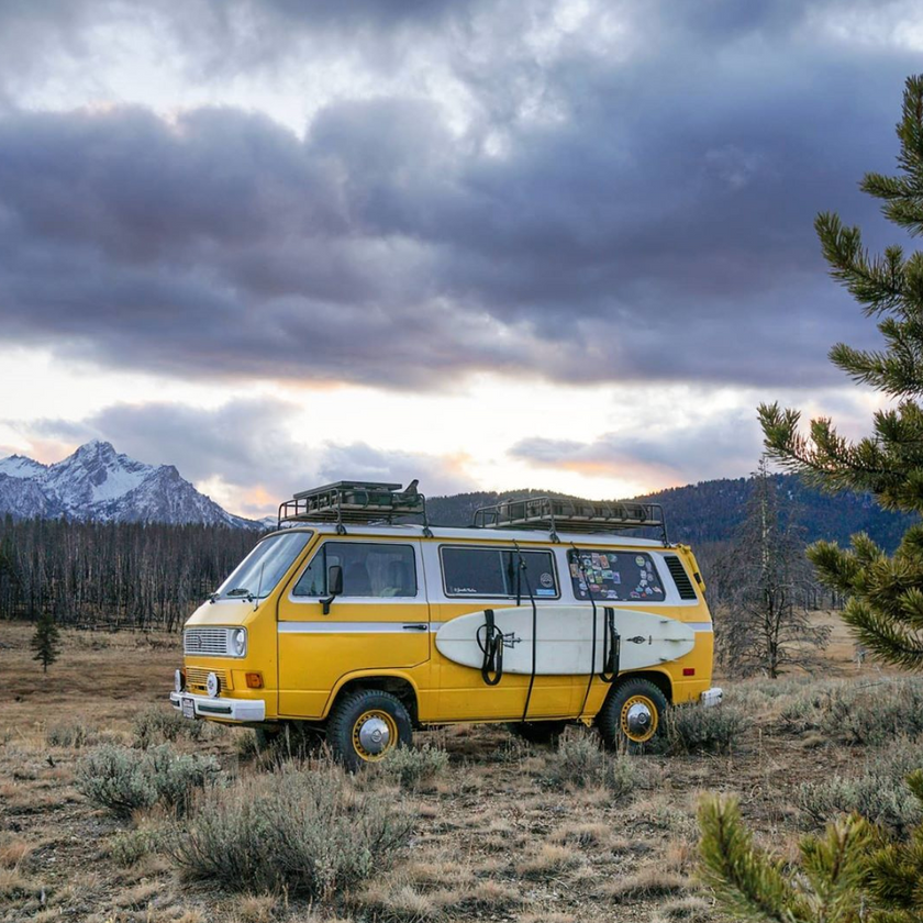 Beautiful yellow retro VW Transporter T3 camper van conversion with surfboard and roof rack in the mountains