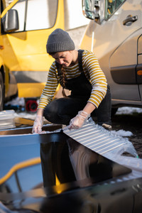 girl in dungarees glueing a window to install on a van conversion
