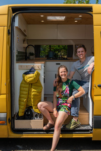 Couple sit in doorway of yellow Mercedes Sprinter van conversion