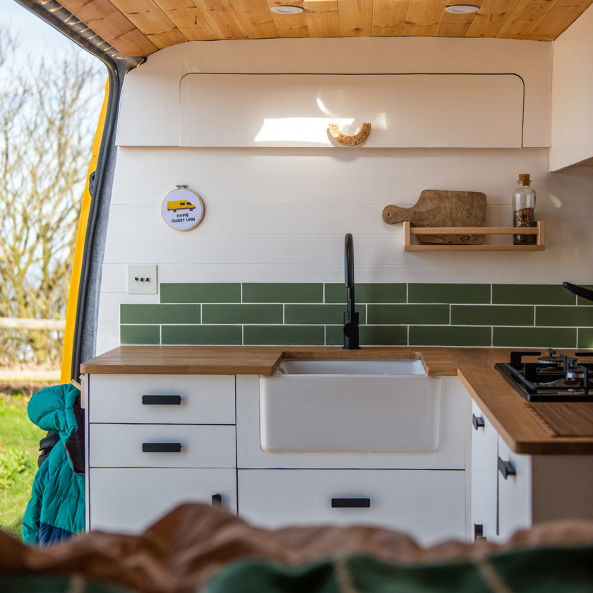 Beautiful Scandi style modern kitchen with Belfast sink and tiles in a camper van conversion
