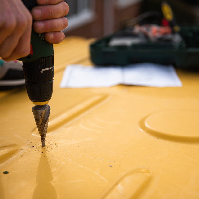 using a step drill bit to drill a hole in a yellow Sprinter van conversion to install a skylight