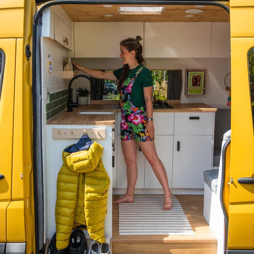 Girl in floral dungarees inside a Scandi camper van kitchen