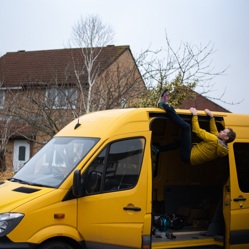 male climber using a heel hook to rock over onto the top of a yellow Sprinter van conversion