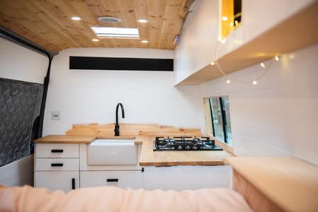 Half painted kitchen inside a Sprinter camper van conversion with a Belfast sink