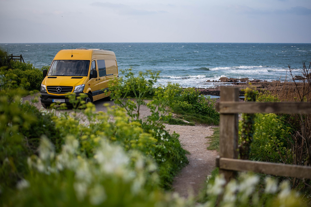 Yellow Mercedes Sprinter van conversion in front of an idyllic landscape Cornwall sea travel