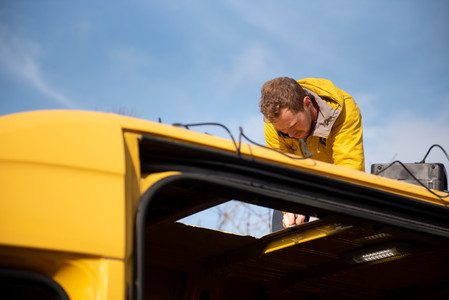man cutting a hole in a yellow Sprinter van conversion with a Jigsaw to install a skylight