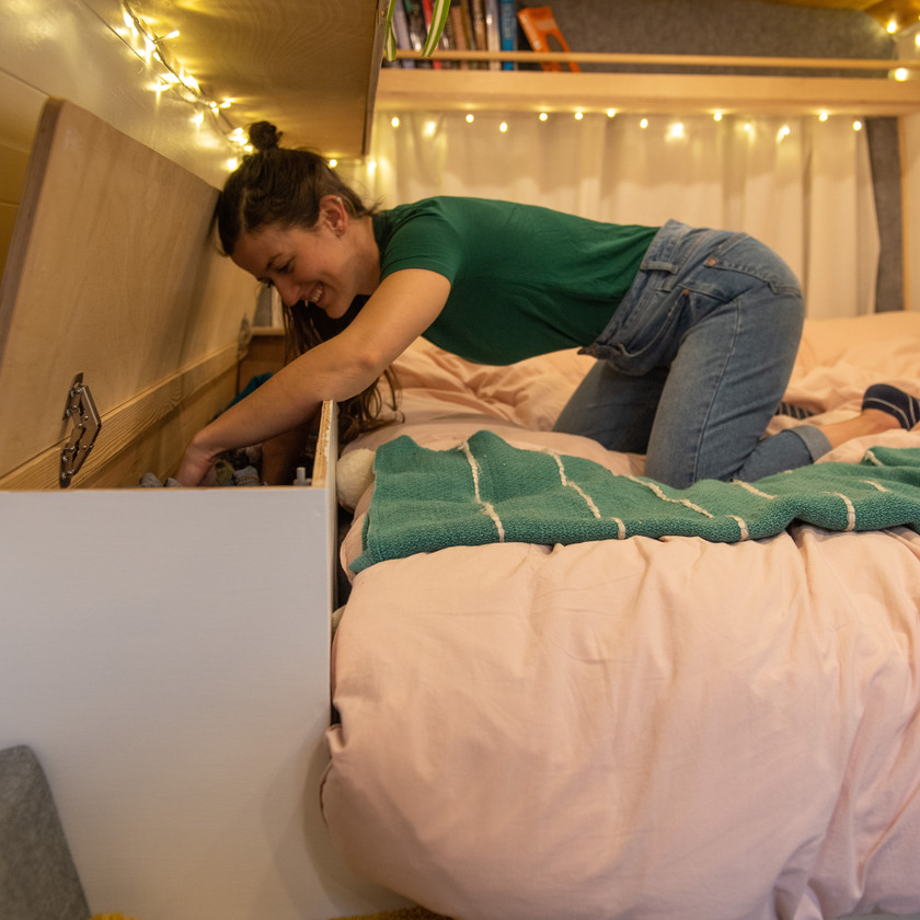 Girl searches through bedside table storage next to fixed bed in a camper van conversion