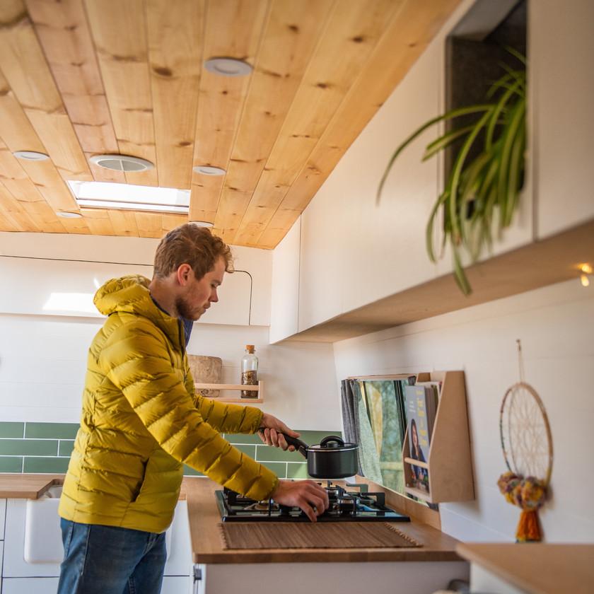Man cooks breakfast in a clean white scandi vibe Sprinter camper van kitchen