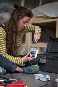 Girl wiring a light switch into a camper van electrical system