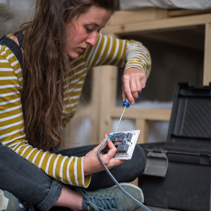Girl wires in plug in a camper van electrical system