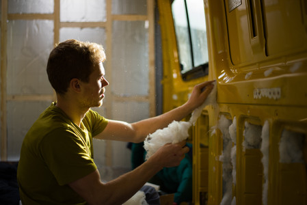 man stuffing ThermaFleece SupaSoft recycled PET bottle wool into a van conversion for insulation