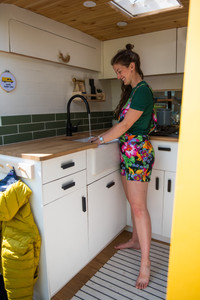 Woman washing up in a Belfast sink in a beautiful campervan conversion