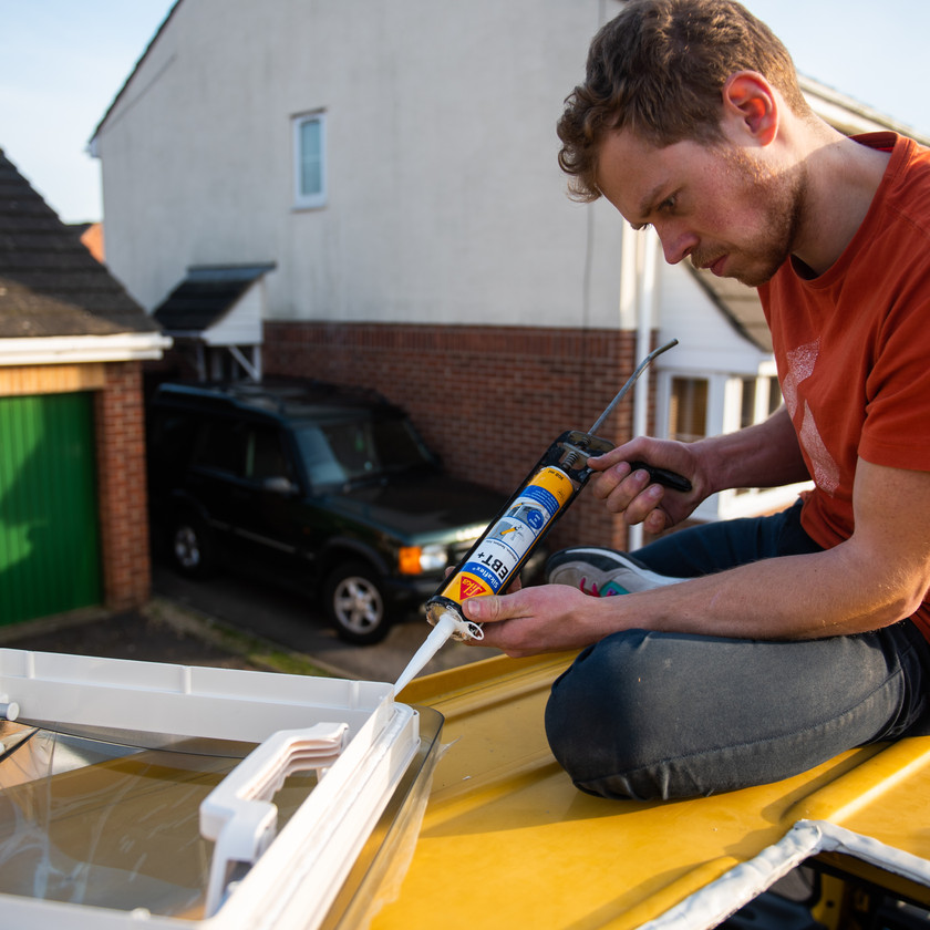 man glueing a skylight in order to install it onto a Sprinter van conversion