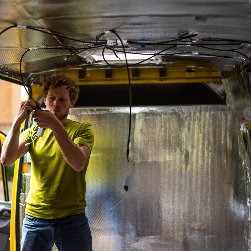 Man wiring lights into a van conversion electrical system